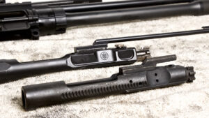 Direct Impingement vs Gas Piston AR-15s disassembled on a table