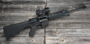 An AR-15 first rifle displayed on a wood background