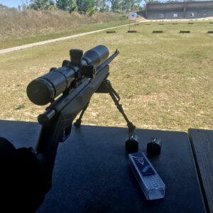 A rifle with an optic pointed down range as the author demonstrates rifle accuracy drills.