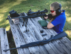 A young shooter firing his first rifle at the range.