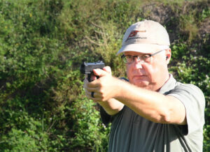 The author shooting the Ruger Security 9 at a shooting range as part of his pistol review.